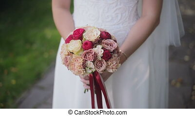 The bride holds a wedding bouquet in hands