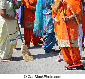Barefoot women sweep the way during the sikh religion...