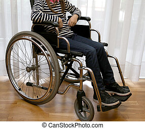 young disabled child in a wheelchair in her bedroom