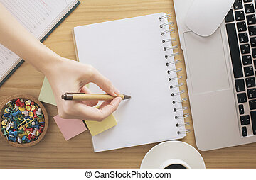 Woman writing in notepad top - Top view of woman's hand...