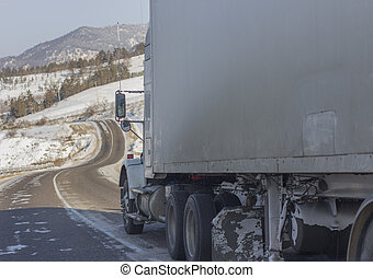 Speeding truck wheels on icy road during winter storm