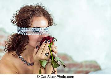 Beautiful woman smells red rose - Close up portrait of a...