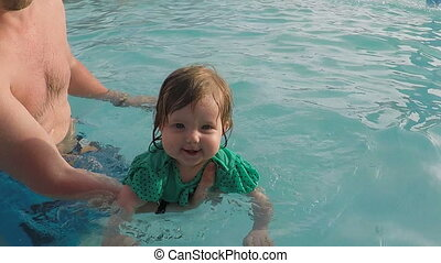 Father teaching baby girl to swim in the swimming pool,...
