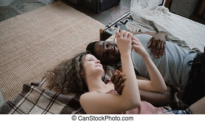 Multiethnic couple lying on bed. Man and woman laughing,...