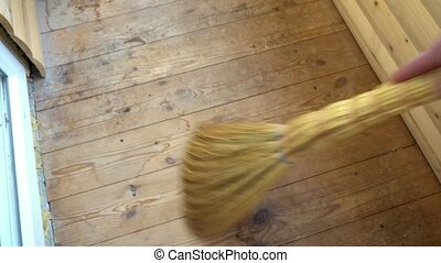 man sweeping the wooden floor,side view.