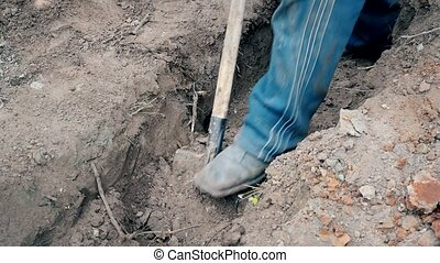 Man digging a trench with a spade with only his feet visible