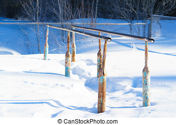 metallic gymnastic bars on the street in the snow. -...
