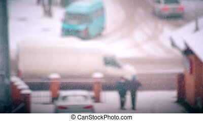 Snow falling on blurred city road landscape background with...