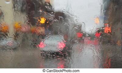 Car stops and pedestrians cross - View through wet...