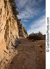 Rocky Cliff Trail Heading Uphill with cloudy sky above