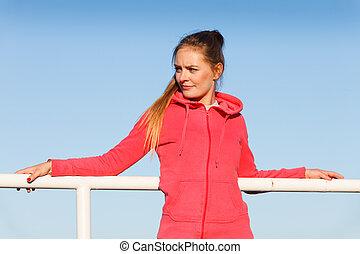 Woman in sportswear standing on dyke by sea - Outdoor relax,...