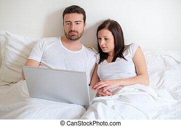 Happy couple searching for consumer advice in internet -...