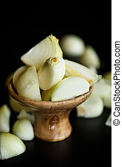 Onion peeled in a wooden bowl