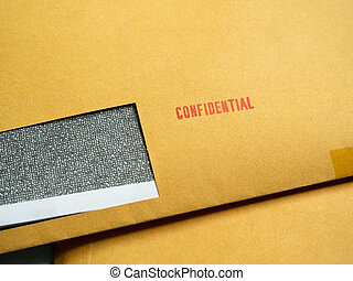"Red ""Confidential"" word printed on brown vintage envelope. Business confidential concept."