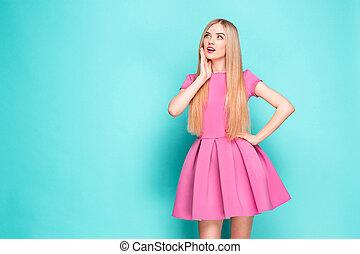 Smiling beautiful young woman in pink mini dress posing,...