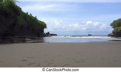 waves of the sea roll on the stony coast, Bali, Indonesia -...