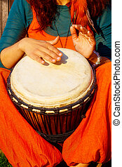 Young lady drummer with her djembe drum. - Young lady...