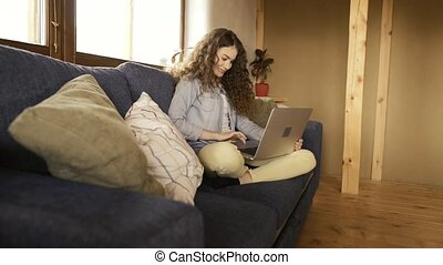 Beautiful teenage girl at home sitting on couch working on...