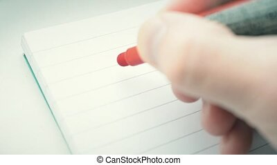 Hand writing the word GOAL with red marker in notepad with...