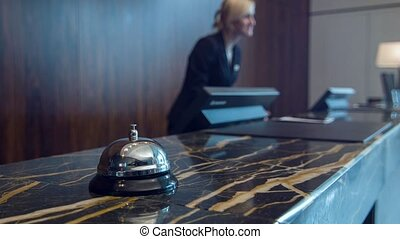 Service bell standing on marble reception desk - At...