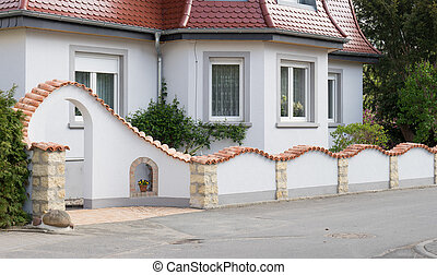 Detached house with wall and entrance