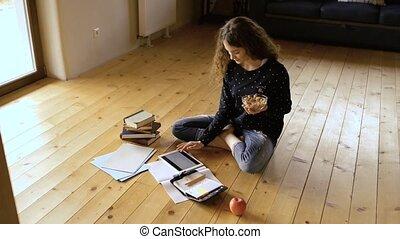 Teenage girl sitting on the floor, studying, eating granola....