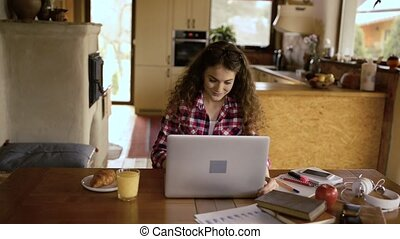 Teenage girl at home, working on notebook, studying -...