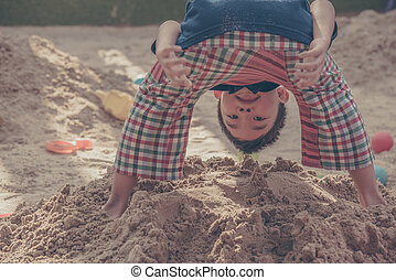 young asian boy playing in sand pit. - vintage tone image of...