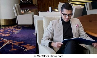 Satisfied handsome man checking up business document - As...