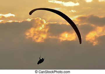 Paragliding Silhouette - A silhouette of a man paragliding...