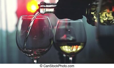 White wine poured into glass in slow motion on the holiday table with lights bokeh on the background. 1920x1080