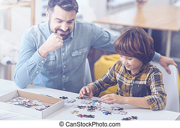 Bearded father and son playing with jigsaw puzzle - Having a...