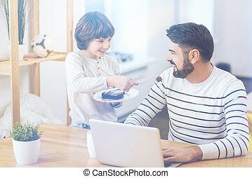Cute little boy feeding his dad - Now your turn, daddy....