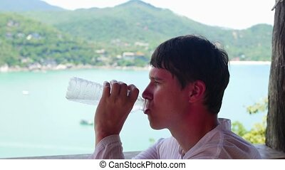 The guy drinks water on a hot day. Panoramic view of the sea and mountains