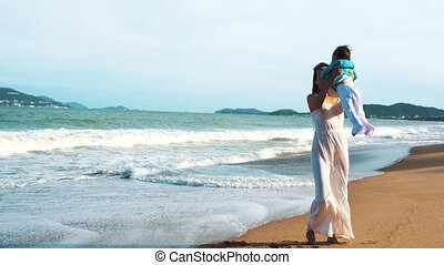 A mother holds her little daughter in her arms on the beach.