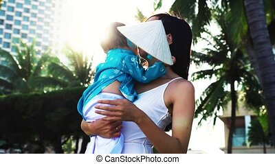 A mother holds her little daughter in her arms on the beach near palms.
