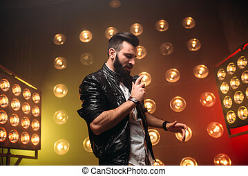 Brutal bearded singer with microphone sing a song on the...