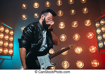 Male musican with electro guitar solo concert