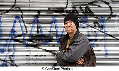Asian senior traveler with urban grung graffiti background...