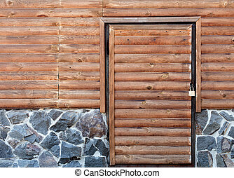 Wooden door to the utility room of a house standing on a stone foundation