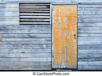 Wooden old weather-beaten barn with a yellow old door
