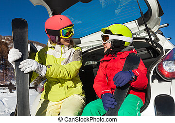 Mom and kid having rest after skiing in car trunk