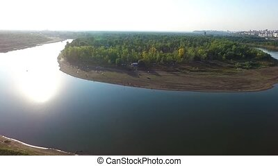 A river in the middle of a forest close to the city. Aerial...
