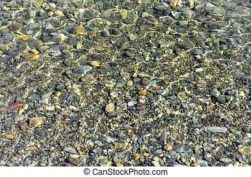 Multicolored pebbles under the water under the sunlight as a...
