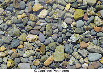 Multicolored pebbles under the water as a background