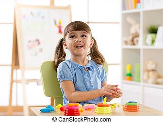 Child playing plasticine in kindergarten.
