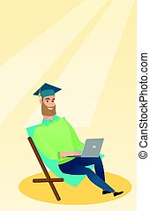 Graduate sitting in chaise lounge with laptop. - Caucasian...