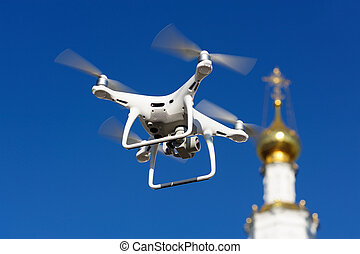 Drone hovering near gilded church dome with orthodox cross...