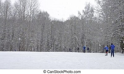 Young athletes have to ski with ski poles under heavy...
