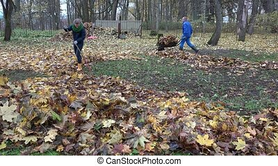 Family man and woman rake and compost leaves together in household yard. 4K